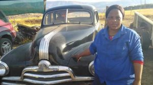 SBA participant in front of one of her classic cars that she restores