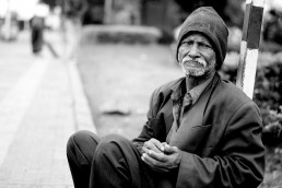 Grayscale image of elderly sitting on street